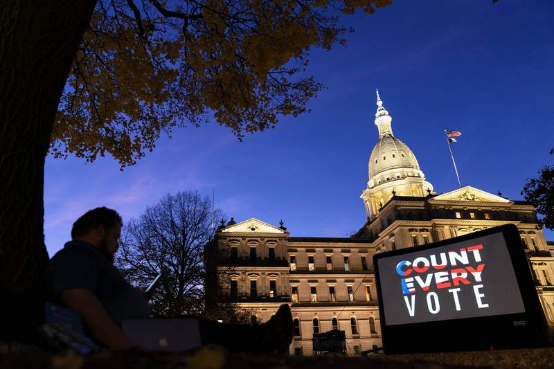 """FILE - In this Nov. 6, 2020, file photo, the phrase """"Count Every Vote"""" is displayed on a large screen, organized by an advocacy group in front of thesState Capitol while election results in several states had yet to be finalized, in Lansing, Mich. (AP Photo/David Goldman, File)"""