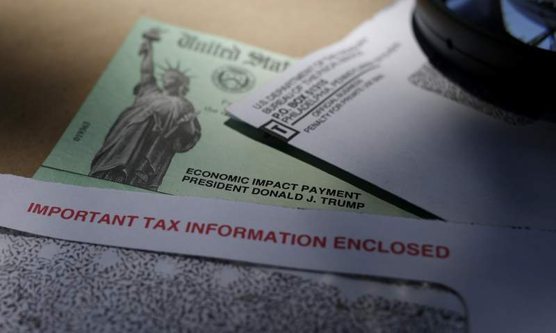 FILE - In this April 23, 2020, file photo, President Donald Trump's name is seen on a stimulus check issued by the IRS to help combat the adverse economic effects of the COVID-19 outbreak, in San Antonio. The U.S. Treasury and IRS have sent out the bulk of the second economic impact payments, which are intended to provide some relief to Americans. However, frustration is high among millions of people who did not receive payments yet and must wait for the mail or file their taxes before they receive it. (AP Photo/Eric Gay, File)