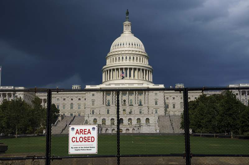 The U.S. Capitol is seen under dark skies in Washington, Tuesday, June 8, 2021, as barriers remain six months after the Jan. 6 attack. A Senate report examining security failures surrounding the Jan. 6 insurrection at the U.S. Capitol blames missed intelligence, poor planning and multiple layers of bureaucracy for the deadly siege. (AP Photo/J. Scott Applewhite)