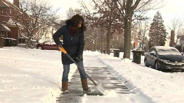 A woman shoveling snow in Michigan (WDIV)