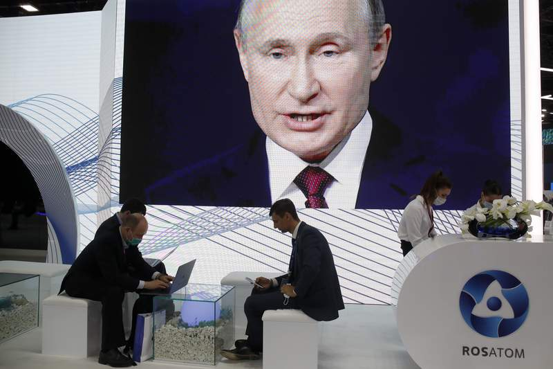 People work in the press center as they listen to Russian President Vladimir Putin speaking, at the St. Petersburg International Economic Forum in St. Petersburg, Russia, Friday, June 4, 2021. (AP Photo/Dmitri Lovetsky)
