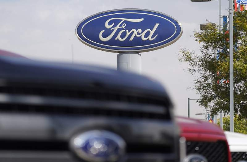 FILE - In this Sunday, Oct. 11, 2020, file photo, the company logo hangs over a row of 2020 F-150 pickup trucks at a Ford dealership, in Denver. A global semiconductor shortage and a February 2021 winter storm have combined to force Ford to build F-150 pickup trucks without some computers. The company says the pickups will be held at factories for a number of weeks, then shipped to dealers once computers are available and quality checks are done. (AP Photo/David Zalubowski, File)
