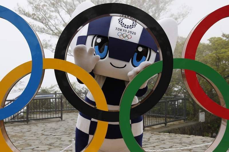 FILE - In this April 14, 2021, file photo, Tokyo 2020 Olympic Games mascot Miraitowa poses with a display of Olympic Symbol after an unveiling ceremony of the symbol on Mt. Takao in Hachioji, west of Tokyo to mark 100 days before the start of the Olympic Games. Japan is set to raise the coronavirus alert level in Tokyos three neighboring prefectures and a forth area in central Japan to allow tougher measures as a more contagious coronavirus variant spreads and doubts are growing whether the Olympics can go ahead. (Kim Kyung-Hoon/Pool Photo via AP)