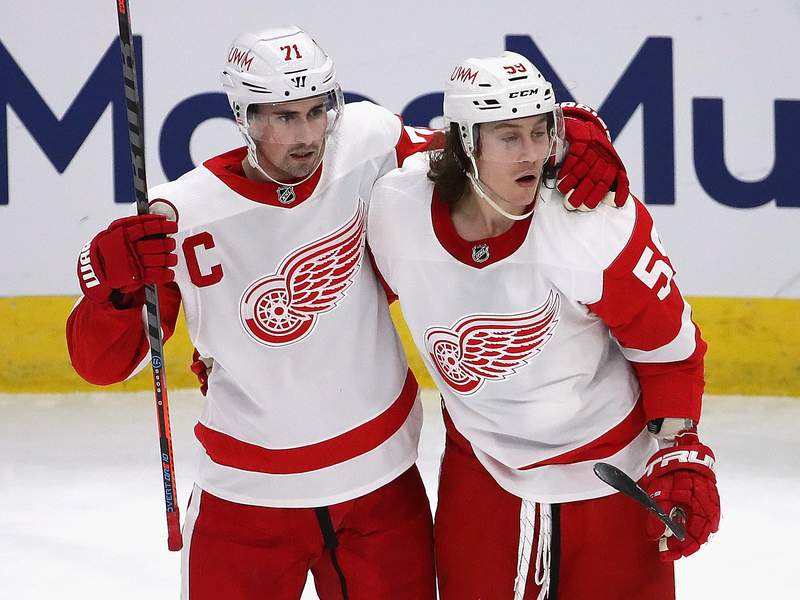CHICAGO, ILLINOIS - JANUARY 24: Tyler Bertuzzi #59 of the Detroit Red Wings (R) gets a hug from Dylan Larkin #71 after scoring a third period goal against the Chicago Blackhawks at the United Center on January 24, 2021 in Chicago, Illinois. The Blackhawks defeated the Red Wings 6-2. (Photo by Jonathan Daniel/Getty Images)