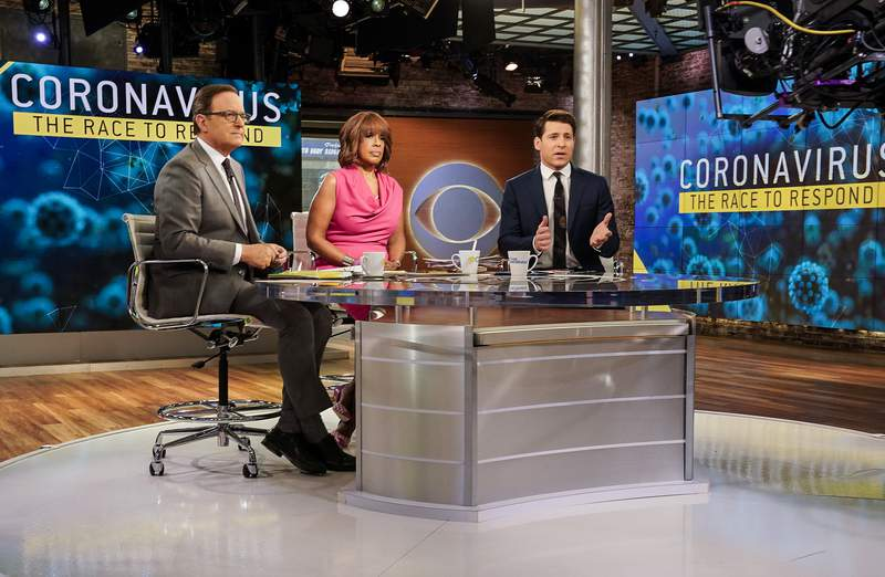 """This March 6, 2020 photo released by CBS shows co-hosts, from left, Anthony Mason, Gayle King and Tony Dokoupil reporting on the coronavirus on """"CBS This Morning"""" in New York. CBS News shut down its New York City headquarters for cleaning and disinfecting on Wednesday, March 11, after two of its employees tested positive for coronavirus. Employees will be asked to work remotely for the next two days and broadcasts moved to accommodate the cleaning, the network said. For instance, CBS This Morning will originate out of Washington on Thursday and Friday while the New York offices are cleaned. For most people, the new coronavirus causes only mild or moderate symptoms. For some it can cause more severe illness. (Michele Crowe/CBS via AP)"""