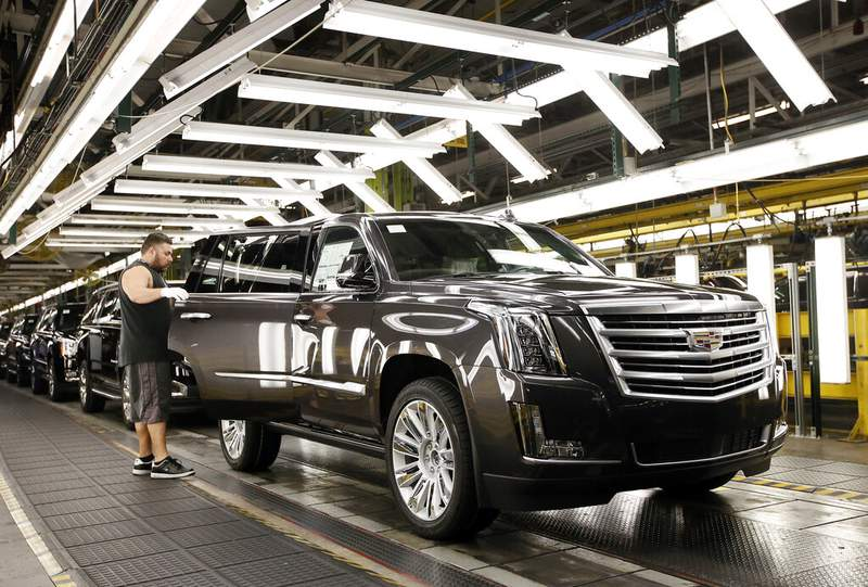 FILE - In this July 14, 2015, file photo, employee Efren Martin II inspects a Cadillac Escalade as it nears the final process of assembly at the General Motors plant in Arlington, Texas. General Motors Co. announced Tuesday, June 25, 2019, that it is investing more than $4.2 billion in assembly plants in Indiana, Michigan and Texas to prepare for the launch of its next generation of pickups and SUVs. (AP Photo/Tony Gutierrez, File)