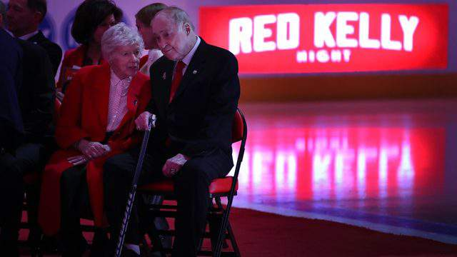 Red Kelly talks to his wife Andra during a ceremony to retire his No. 4 prior to a game against the Toronto Maple Leafs at Little Caesars Arena on February 01, 2019 in Detroit, Michigan. (Photo by Gregory Shamus/Getty Images)