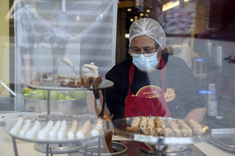 FILE - In this May 14, 2021, file photo, a worker wears a mask while prepares desserts at the Universal City Walk, in Universal City, Calif. California workplace regulators are considering Thursday, June 3, 2021, whether to end mask rules if every employee in a room has been fully vaccinated against the coronavirus, frustrating business groups by eying a higher standard than the state plans to soon adopt for social settings. (AP Photo/Marcio Jose Sanchez, File)