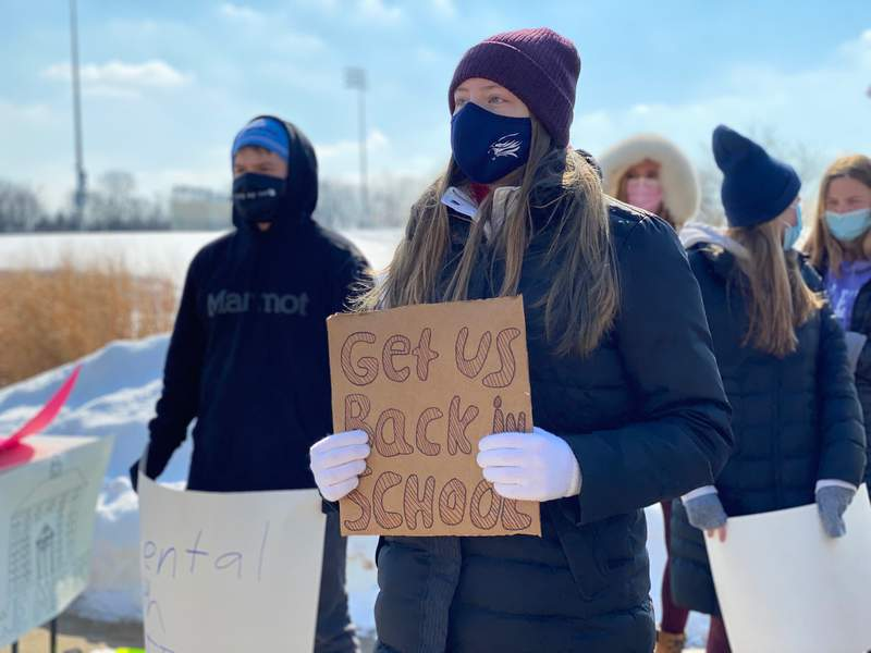 A high school student holds up a sign at a protest outside Skyline High School in Ann Arbor on Feb. 20, 2021.