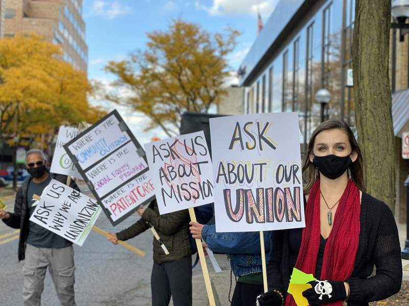 Lisa Conine pickets with others outside Om of Medicine in downtown Ann Arbor on Oct. 16, 2020.