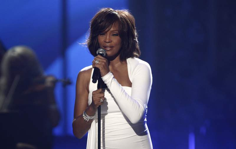 FILE - In this Nov. 22, 2009 file photo, Whitney Houston performs at the 37th Annual American Music Awards in Los Angeles. A feature film about Houstons life is in the works from Anthony McCarten, the screenwriter of Bohemian Rhapsody. The biopic is being shepherded by the Whitney Houston Estate, music producer Clive Davis and Primary Wave Music, the partners said Wednesday. (AP Photo/Matt Sayles)