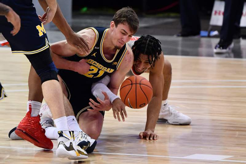 Franz Wagner #21 of the Michigan Wolverines and Justice Sueing #14 of the Ohio State Buckeyes battle for a loose ball on the floor in the first half at Value City Arena on February 21, 2021 in Columbus, Ohio.