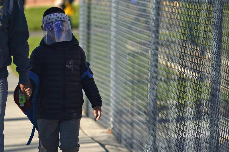 A student wears a mask and face shield while arriving at Newhall Elementary School Thursday, Feb. 25, 2021, in Santa Clarita, Calif. (AP Photo/Marcio Jose Sanchez)