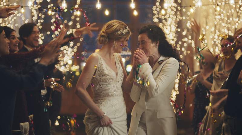 """This image made from undated video provided by Zola shows a scene of its advertisement. The Hallmark Channel says it will reinstate same-sex marriage commercials that it had pulled from the network. Hallmark Cards CEO Mike Perry said in a statement Sunday, Dec. 15, 2019, that pulling the commercials was the wrong decision.""""  (Zola via AP)"""