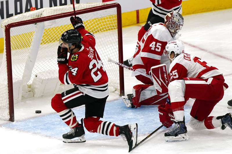 Chicago Blackhawks center Pius Suter, left, reacts after scoring his second goal as Detroit Red Wings goalie Jonathan Bernier and defender Danny DeKeyser react during the first period of an NHL hockey game in Chicago, Sunday, Jan. 24, 2021. (AP Photo/Nam Y. Huh)