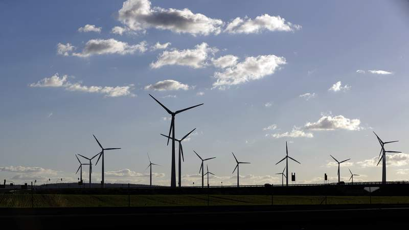 FILE-In this Oct. 4, 2016 taken photo wind turbines spin near Halle, central Germany. (AP Photo/Matthias Schrader)