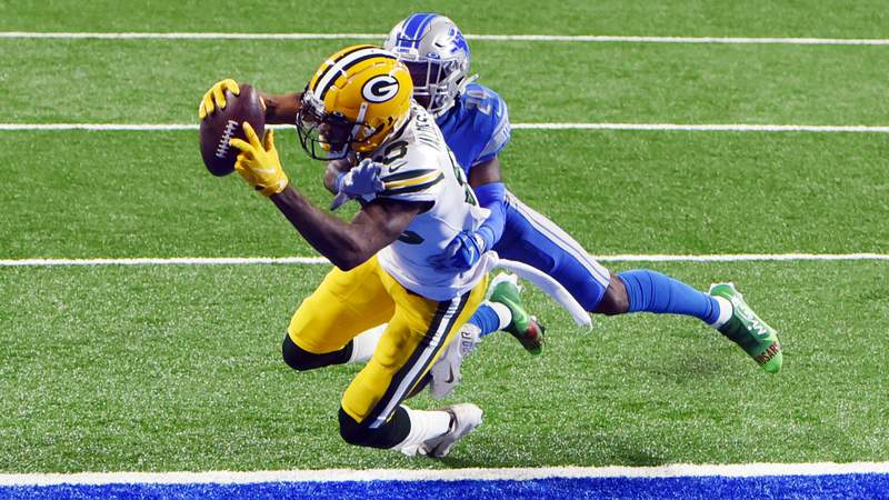 Marquez Valdes-Scantling #83 of the Green Bay Packers scores a touchdown during the second quarter against Amani Oruwariye #24 of the Detroit Lions at Ford Field on December 13, 2020 in Detroit, Michigan.