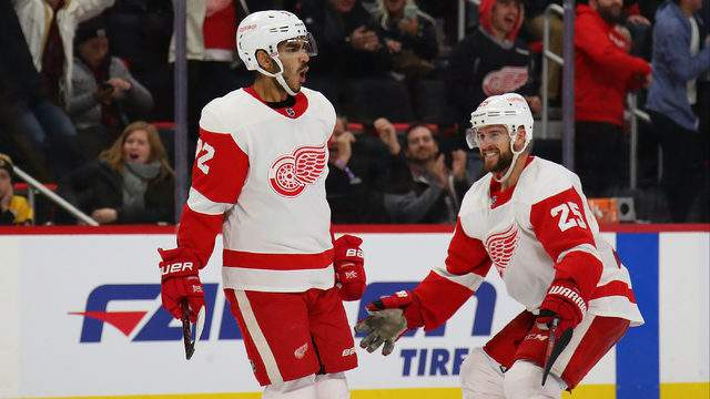 Andreas Athanasiou of the Detroit Red Wings celebrates his game winning overtime goal with Mike Green to defeat the Boston Bruins 3-2 at Little Caesars Arena on November 21, 2018 in Detroit, Michigan. (Photo by Gregory Shamus/Getty Images)