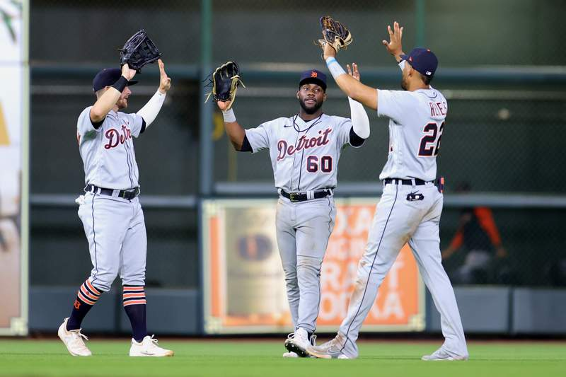 Robbie Grossman #8, Akil Baddoo #60 and Victor Reyes #22 of the Detroit Tigers celebrate an 8-2 win over the Houston Astros at Minute Maid Park on April 13, 2021 in Houston, Texas.