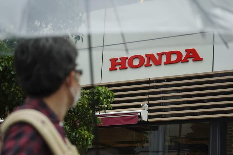 A man wearing a protective mask to help curb the spread of the coronavirus walks past the logo of Honda Motor Company Thursday, May 13, 2021, in Tokyo. (AP Photo/Eugene Hoshiko)