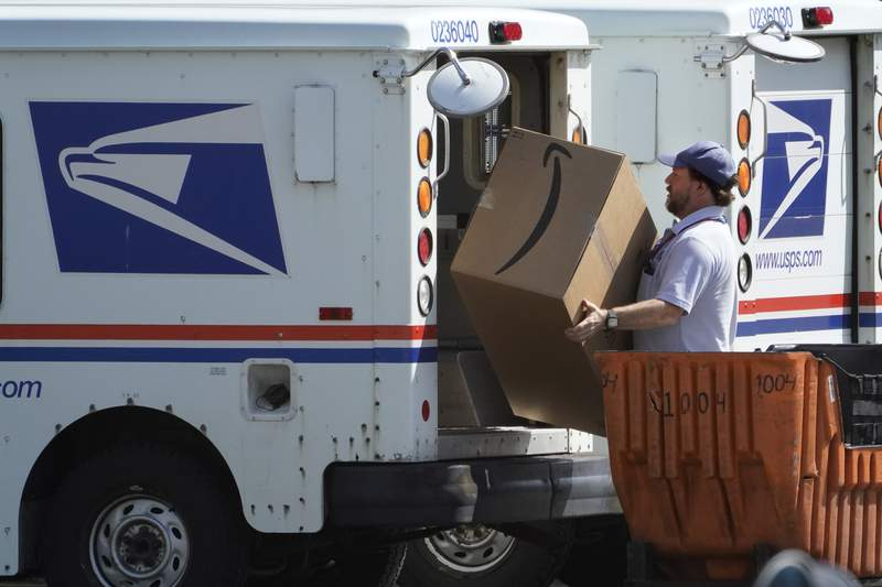 An Amazon package is loaded onto a U.S. Postal Service truck, Tuesday, Aug. 18, 2020, Portland, Maine. Facing public pressure and state lawsuits, the Postmaster general announced Tuesday he is halting some operational changes to mail delivery that critics warned were causing widespread delays and could disrupt voting in the November election. (AP Photo/Robert F. Bukaty)