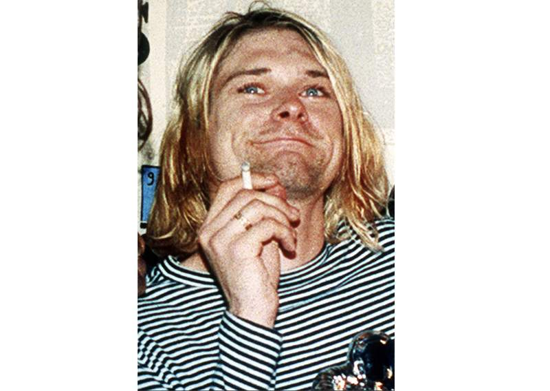 FILE - This 1993 file photo shows Kurt Cobain, the lead singer of the U.S. rock band Nirvana. Six strands of blonde hair from the grunge rock icon are part of a series of Nirvana offerings that also includes a Cobain amp and a rare group-signed blue Stratocaster-style guitar at an online rock n roll auction that ends over the weekend..  (AP Photo/Mark J. Terrill, File)