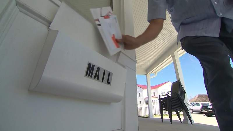 A Postal Service worker delivers mail to a box in this undated file image.