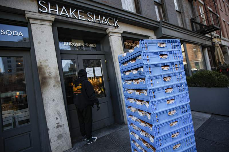 FILE - In this March 16, 2020, file photo, a bread delivery is made to a Shake Shack restaurant in the Brooklyn borough of New York. The burger chain Shake Shack says it will return a small-business loan it got to help weather the coronavirus crisis after topping up its funding. (AP Photo/John Minchillo, File)