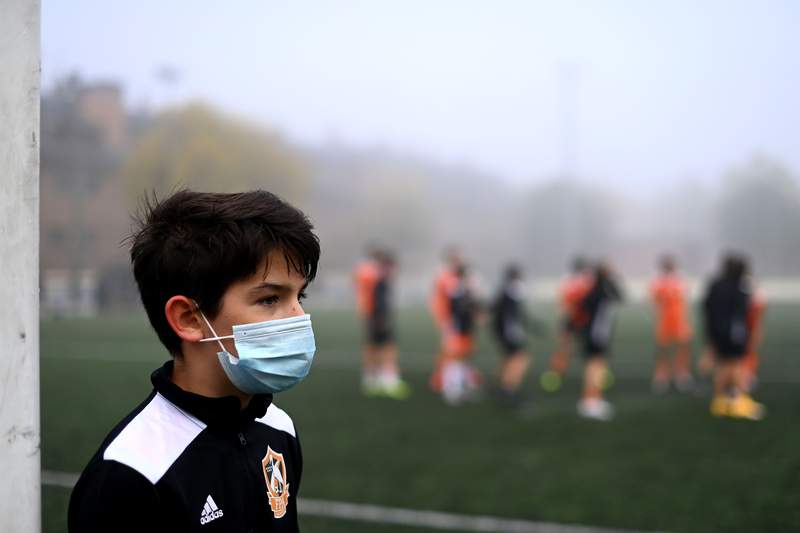A boy wearing a face mask to protect against the spread of the novel coronavirus attends a football match with his team of Football Player Academy (FPA) Las Rozas in Las Rozas, outside Madrid, on October 24, 2020. - Mandatory on the street for months, the mask has also become the norm in the sports grounds of some Spanish regions, occasionally with considerable difficulties. (Photo by Gabriel BOUYS / AFP) (Photo by GABRIEL BOUYS/AFP via Getty Images)