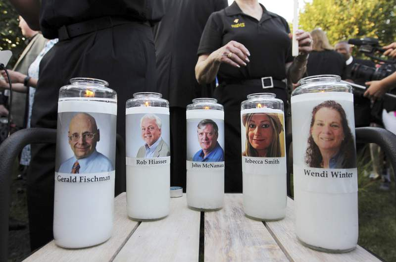 FILE - In this June 29, 2018, file photo, photos of five employees of the Capital Gazette newspaper adorn candles during a vigil across the street from where they were slain in the newsroom in Annapolis, Md. Jarrod Ramos, who killed the five told a state psychiatrist there is no defense for the crimes he committed and that he would kill more people if he were somehow acquitted, because he wanted to be incarcerated, attorneys said Wednesday, June 9, 2021 during a court hearing. (AP Photo/Jose Luis Magana, File)