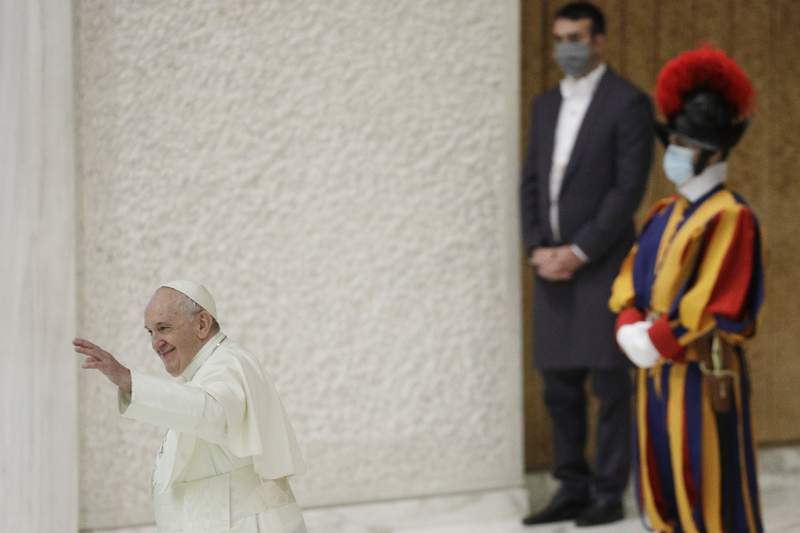 Pope Francis waves at the end of his weekly general audience in the Paul VI hall at the Vatican, Wednesday, Oct. 21, 2020. Pope Francis endorsed same-sex civil unions for the first time as pope while being interviewed for the feature-length documentary Francesco, which premiered Wednesday at the Rome Film Festival. (AP Photo/Gregorio Borgia)