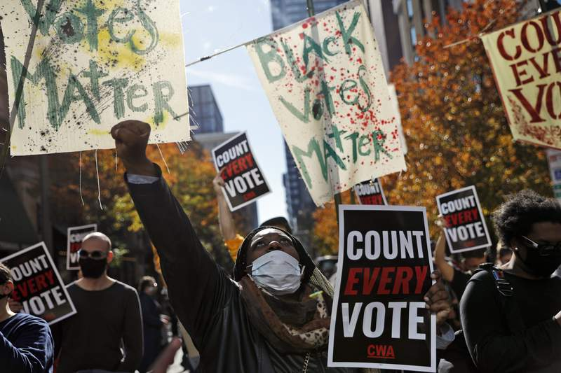 Zhanon Morales, 30, of Philadelphia, raises her fist as demonstrators call for all votes be counted during a rally outside the Pennsylvania Convention Center, Thursday, Nov. 5, 2020, in Philadelphia, as vote counting in the general election continues. (AP Photo/Rebecca Blackwell)