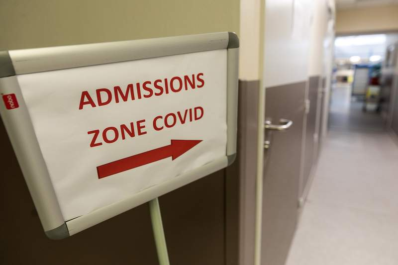 A sign is pictured at the entrance of the COVID ward of the Hautepierre hospital in Strasbourg, eastern France, Thursday, Nov.12, 2020. France has confirmed more virus infections in the pandemic than any other European country, and positive cases had been rising steadily since July. But over the past 10 days, the number of cases per 100,000 people has been dropping. (AP Photo/Jean-Francois Badias)