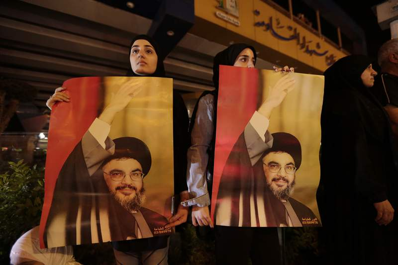 FILE - In this Oct. 25, 2019 file photo, supporters of Hezbollah leader Sayyed Hassan Nasrallah hold his picture, in the southern suburbs of Beirut, Lebanon. Nasrallah has thrown his support behind the Lebanese government seeking financial assistance from the International Monetary Fund but said it should negotiate the conditions cautiously. Nasrallahs comments on Monday, May 4, 2020, came four days after the countrys prime minister said Lebanon will seek a rescue deal from the IMF to help the nation find a way out of a crippling financial crisis. (AP Photo/Hassan Ammar, File)