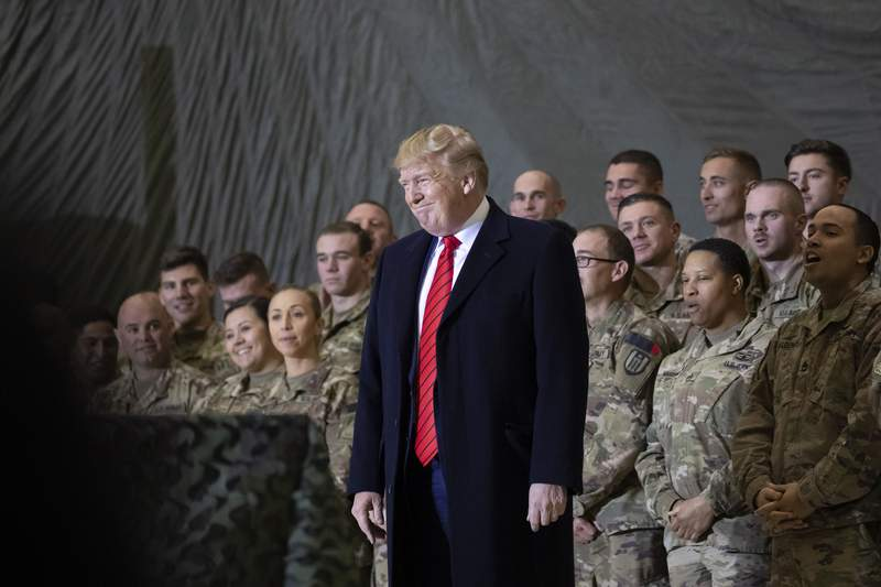 FILE - In this Nov. 28, 2019, file photo President Donald Trump smiles before addressing members of the military during a surprise Thanksgiving Day visit at Bagram Air Field, Afghanistan. Trump has held himself up as a champion of U.S. troops without rival. Now, with his presidency on the line, hes casting suspicion on a tool of participatory democracy, the mail-in ballot, that has allowed U.S. military personnel to participate in elections while serving far from home since the War of 1812. (AP Photo/Alex Brandon, File)