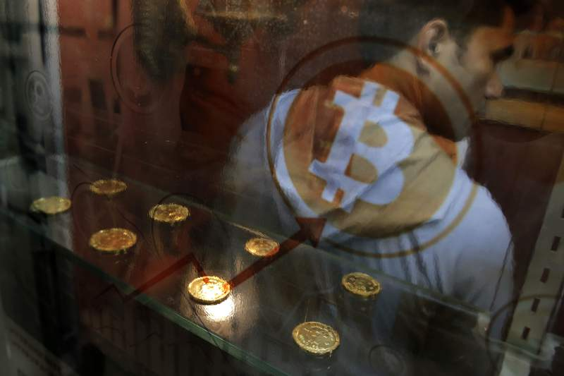 FILE- In this Dec. 8, 2017, file photo, a man uses a Bitcoin ATM in Hong Kong.   Digital currency exchange Coinbase is looking to become a publicly traded company, a move being hailed by some as a start to helping cryptocurrency gain more mainstream acceptance. Coinbase Global Inc., in a filing with the Securities and Exchange Commission, is seeking a direct listing, which would allow company workers and investors to convert their stakes into stock. (AP Photo/Kin Cheung, File)