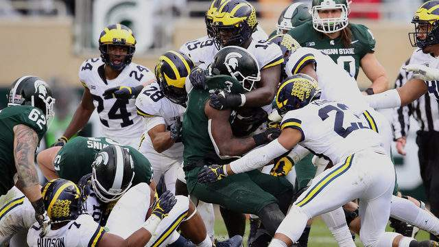 LJ Scott is tackled by the Michigan defense during a second half run at Spartan Stadium on Oct. 20, 2018 in East Lansing, Michigan. (Gregory Shamus/Getty Images)