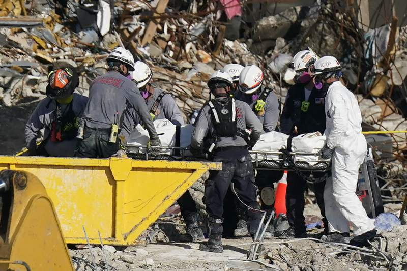 Search and rescue personnel remove remains on a stretcher as they work atop the rubble at the Champlain Towers South condo building where scores of people remain missing more than a week after it partially collapsed, Friday, July 2, 2021, in Surfside, Fla. Rescue efforts resumed Thursday evening after being halted for most of the day over concerns about the stability of the remaining structure.(AP Photo/Mark Humphrey)