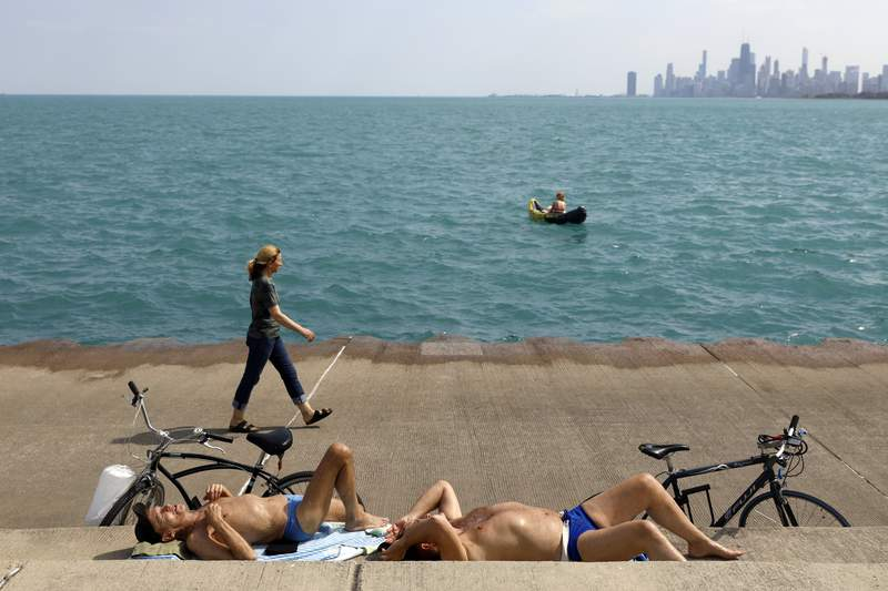 Chet Ski, left and Richard Paul sunbath as others pass along Lake Michigan on Tuesday, April 27, 2021 in Montrose Beach, Chicago. The Centers for Disease Control and Prevention eased its guidelines Tuesday on the wearing of masks outdoors, saying fully vaccinated Americans don't need to cover their faces anymore unless they are in a big crowd of strangers. (AP Photo/Shafkat Anowar)