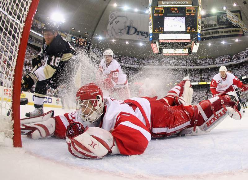 PITTSBURGH - JUNE 04: Marian Hossa #18 of the Pittsburgh Penguins slides the puck through the crease past goaltender Chris Osgood #30 of the Detroit Red Wings in the final seconds of game six of the 2008 NHL Stanley Cup Finals at Mellon Arena on June 4, 2008 in Pittsburgh. Pennsylvania.  The Red Wings defeated the Penguins 3-2 to win the Stanley Cup Finals 4 games to 2.  (Photo by Dave Sandford/Getty Images)