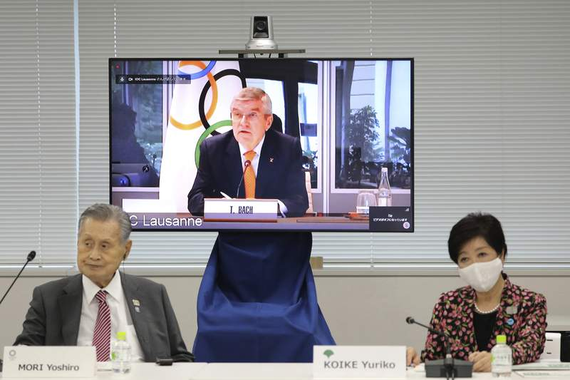In this Sept. 24, 2020, file photo, IOC President Thomas Bach, on the screen, speaks remotely with Tokyo 2020 Organizing Committee President Yoshiro Mori, left, and Tokyo Gov. Yuriko Koike, right, during an on-line meeting focused on how to pull off the delayed Tokyo Games, in Tokyo. The IOC and local organizers are trying to simplify next year's postponed Tokyo Olympics, promising to save money in what one study says is already the most expensive Summer Olympics on record. (Du Xiaoyi/Pool Photo via AP)