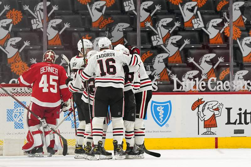 Chicago Blackhawks teammates congratulate left wing Alex DeBrincat after his goal against Detroit Red Wings goaltender Jonathan Bernier (45) during the second period of an NHL hockey game, Saturday, April 17, 2021, in Detroit. (AP Photo/Carlos Osorio)