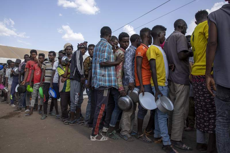 Tigrayan refugees wait in line to revive food from Muslim Aid at Hamdeyat Transition Center near the Sudan-Ethiopia border, eastern Sudan, Wednesday, March 24, 2021. (AP Photo/Nariman El-Mofty)