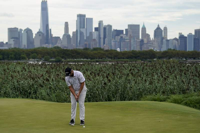 Jon Rahm, of Spain, sinks his putt on the 14th green as the Manhattan skyline looms in the distance in the second round at the Northern Trust golf tournament, Friday, Aug. 20, 2021, at Liberty National Golf Course in Jersey City, N.J. (AP Photo/John Minchillo)