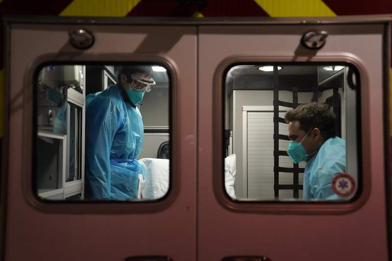 Emergency medical technician Thomas Hoang, left, of Emergency Ambulance Service, and paramedic Trenton Amaro prepare to unload a COVID-19 patient from an ambulance in Placentia, Calif., Friday, Jan. 8, 2021. EMTs and paramedics have always dealt with life and death -- they make split-second decisions about patient care, which hospital to race to, the best and fastest way to save someone, and now they're just a breath away from becoming the patient themselves. (AP Photo/Jae C. Hong)