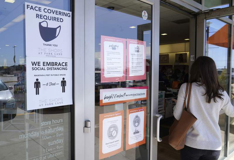 A sign requiring masks and social distancing at a business. (AP Photo/LM Otero)