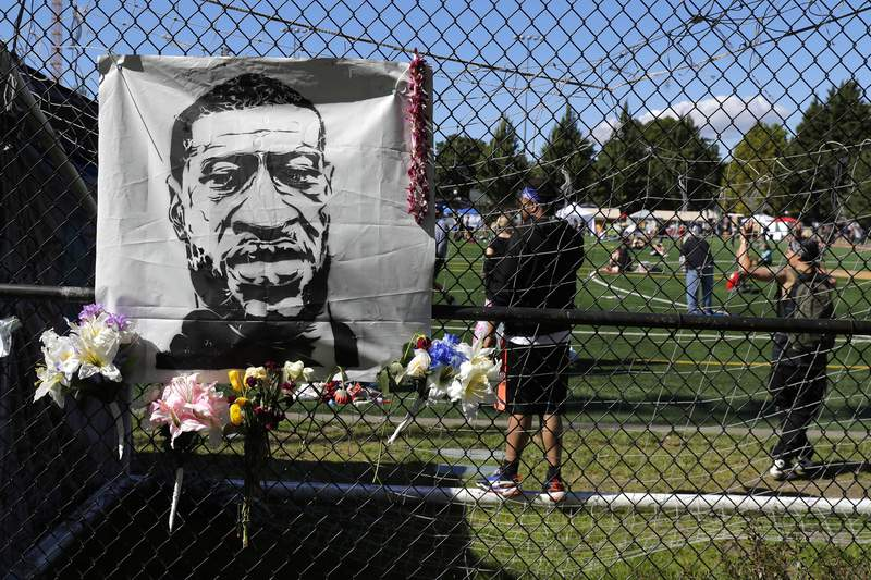 Flowers are placed next to an image of George Floyd on a fence surrounding Cal Anderson Park, Wednesday, June 17, 2020, inside what has been named the Capitol Hill Occupied Protest zone in Seattle. (AP Photo/Ted S. Warren)