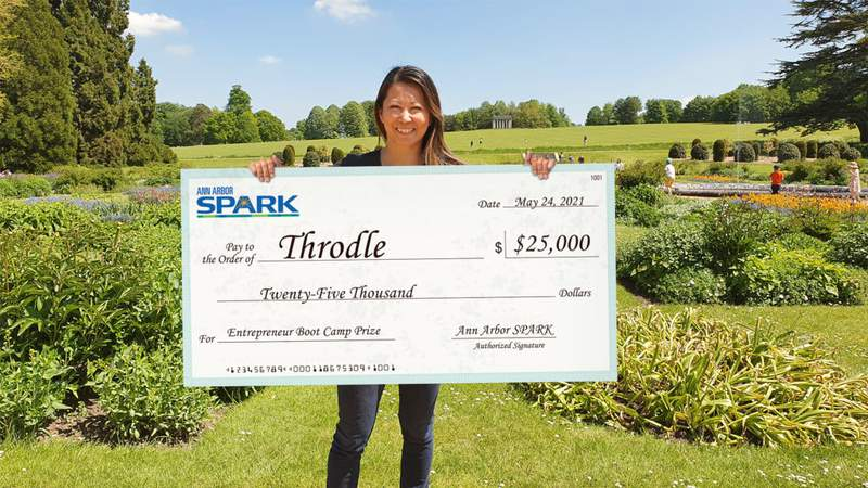 Nadine Lee, Throdle CEO, holds up a check for $25,000 from Ann Arbor SPARK.