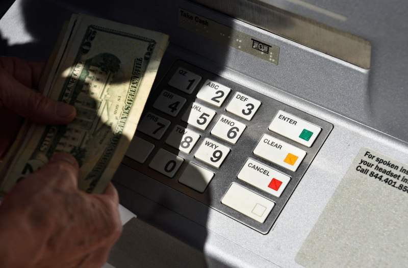 SANTA FE, NEW MEXICO - AUGUST 7, 2018:  A banking customer withdraws money from a ATM machine in Santa Fe, New Mexico. (Photo by Robert Alexander/Getty Images)