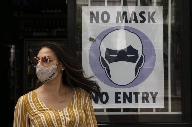 FILE - In this June 23, 2020, file photo, a woman walks out of a liquor store past a sign requesting its customers to wear a mask in Santa Monica, Calif. (AP Photo/Jae C. Hong, File)